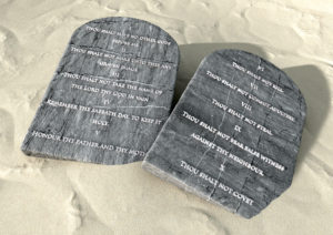 Two stone tablets with the ten commandments inscribed on them lying on brown desert sand